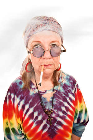 hippy: Senior hippie lady with cigarette in a cloud of smoke