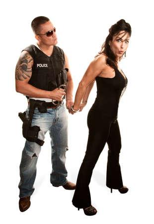 hand cuffs: Macho policeman arresting pretty Latina woman Stock Photo