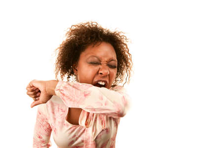 sleeve: Young woman sneezing into her sleeve to prevent disease spread