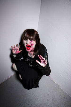 Young female zombie or vampire in a corner photo