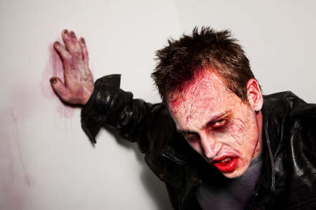 Exhausted bloody zombie leaning against a wall Stock Photo