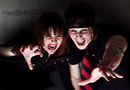 cannibal: Male and female bloody zombies reaching out Stock Photo
