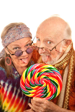 goofy: Portrait of hippie seniors licking a large lollipop Stock Photo