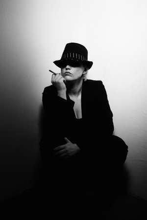 fedora: Mysterious woman crouched in corner with lit cigarette