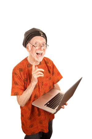 senior ordinateur: Senior computer guru with shiny silver laptop Banque d'images