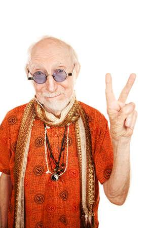 New age senior man in orange shirt making peace sign Stock Photo