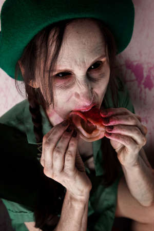 female zombie or alien scout chewing on tasty human ear photo