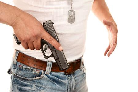 Closeup of man in t-shirt drawing gun from waist