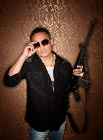 Handsome Hispanic man with a large automatic rifle photo