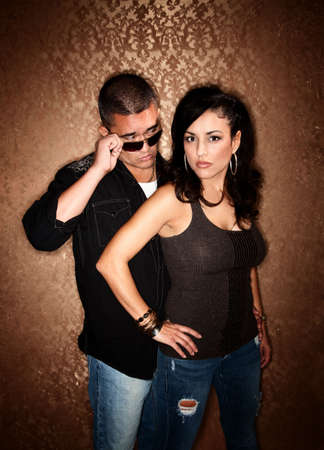 Attractive Hispanic Couple Posing in Front of Gold Background photo