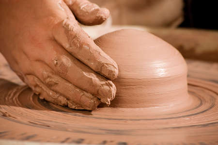 potters wheel: Hand shaping wedge of clay on spinning potters wheel Stock Photo
