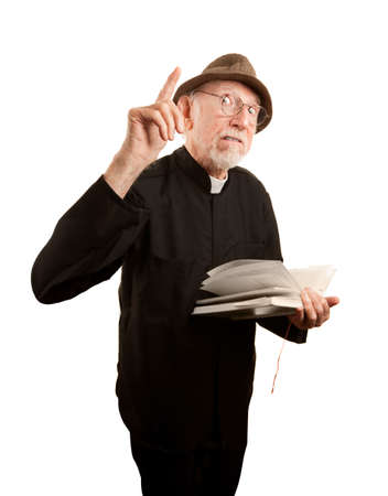 Senior priest or pastor giving a fiery sermon from the Bible photo