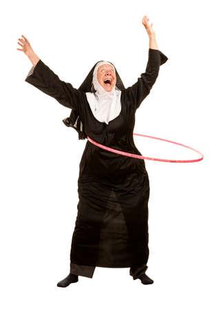 nun: Funny nun in socks excercising with toy plastic hoop