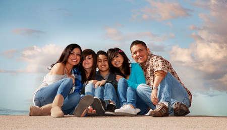 ni�os latinos: Familia hispana sentado contra un cielo nublado Foto de archivo