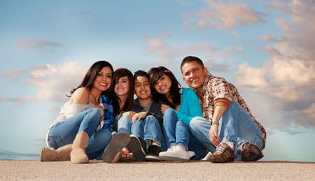 latinos: Hispanic family seated against a cloudy sky