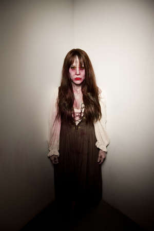 satanist: Bloody village witch or retro zombie in a corner Stock Photo
