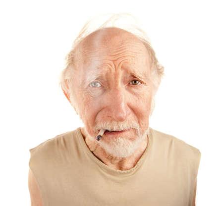 ragged: Indigent senior man in ragged sgirt smoking cigarette Stock Photo