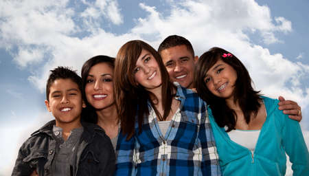 latina girl: Hispanic family seated against a cloudy sky