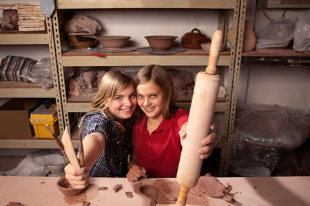 Cute young girls in clay studio holding up shaping tools Фото со стока