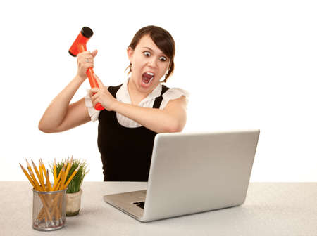 angry women: Pretty female office worker destroying laptop computer Stock Photo
