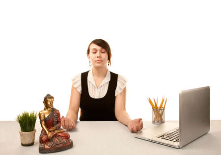 Pretty young woman meditating at her desk photo