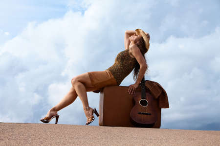 Pretty brunette woman with suitcase and guitar photo