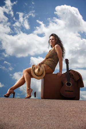 Pretty brunette woman with suitcase and guitar Stock Photo - 6570384