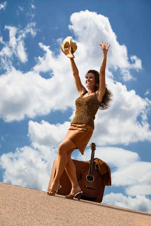 Pretty brunette woman with suitcase and guitar Stock Photo - 6569736
