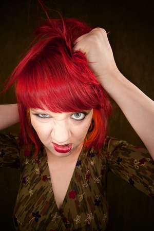 Pretty punky girl with brightly dyed red hair