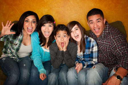 family sofa: Hispanic Family with Big facial Reactions Sitting on Couch