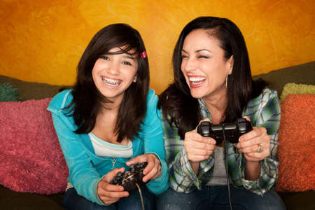 nerd girl: Attractive Hispanic Woman and Girl Playing a Video Game with Handheld Controllers