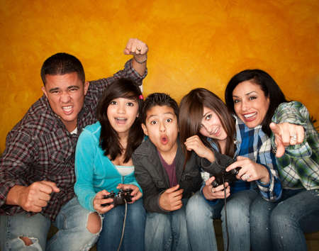 nerd girl: Attractive Hispanic Family on Couch Playing a Video Game