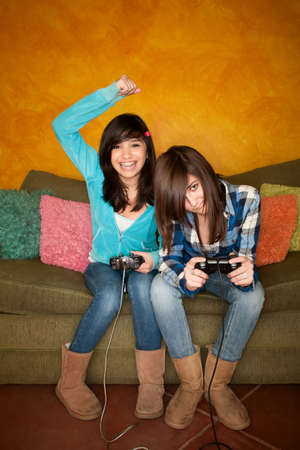 Cute Hispanic Girls Playing a Video Game with Handheld Controllers photo