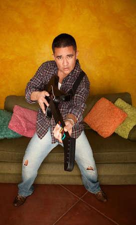 Handsome Hispanic man playing guitar based video game photo