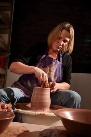 Female potter at wheel shaping clay with wooden jigger