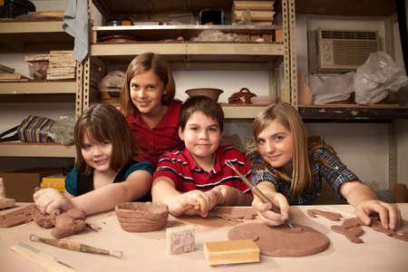 Four cute kids posing in a clay studio