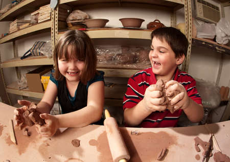 dirty girl: Cute kids working with clay in an art studio