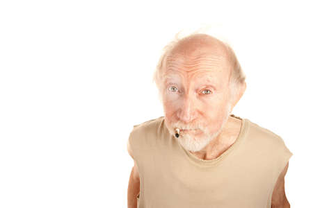 Senior man in ragged shirt smoking the stub of a cigarette Stock Photo - 6569768