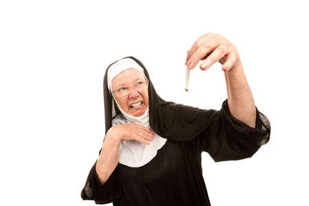 confiscated: Senior suora mostrando disgusto tenendo la sigaretta bruciato Archivio Fotografico