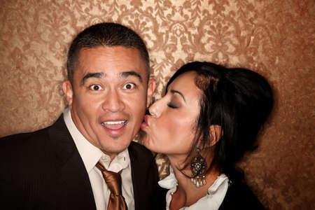 Attractive Hispanic woman giving handsome husband or boyfriend a kiss photo