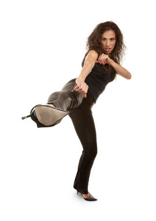 martial arts woman: Tough woman in high heels kicking at camera Stock Photo