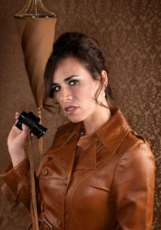 Beautiful Spy with Binoculars in Leather Coat photo