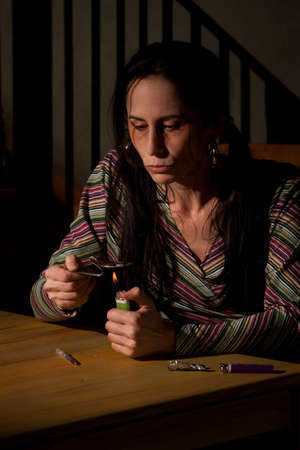 Woman cooking heroin in a bent spoon