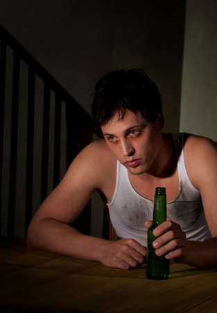 suicidal: Depressed young man with bottle of beer