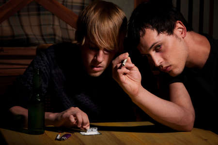 illicit: Due giovani uomini con eroina o cocaina sul tavolo
