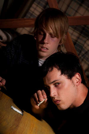opiate: Two young men with heroin or cocaine on table
