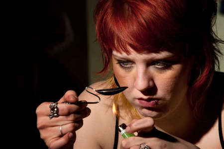 junkie: Young woman cooking heroin in a bent spoon Stock Photo