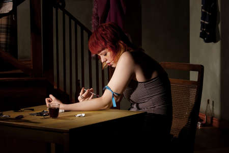 opioid: Woman wih tracks on her arm injecting heroin