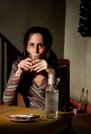 intoxicant: Alcoholic woman with bottle of clear liquor Stock Photo