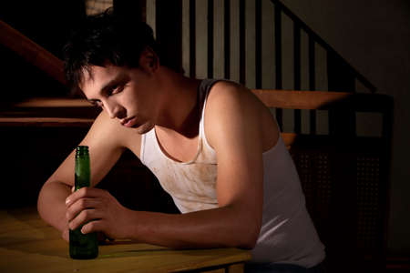 alcoholic: Depressed young man with bottle of beer